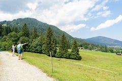 Vati- und Tochterweg in den Bergen und die Nachbarschaft ansehen lizenzfreie stockfotografie
