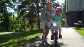 Vati unterrichtet seine Tochter, ein Fahrrad zu reiten stock video