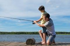 Vati unterrichtet Sohn, auf dem Spinnen von der Bank auf dem Fluss zu fischen lizenzfreies stockfoto