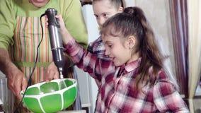 Vati unterrichtet Töchter, ein von, wem mit Down-Syndrom, einen Küchenmischer benutzen stock video