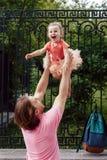 Vati wirft die glückliche Tochter Lizenzfreie Stockfotos