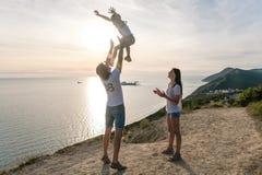 Vati wirft seinen Sohn in der Luft, und Mutter betrachtet sie auf dem Berg mit Meerblick Bringen Sie und seine sechs Monate süße  lizenzfreies stockfoto