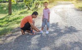 Vatibindung das Seil beschuht seinen Sohn auf Straße im Park lizenzfreie stockfotografie