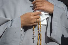 A nun praying the holy Rosary stock images