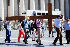 Vatican city center life - pilgrims carry cross. ROME, ITALY - MAY 30: Vatican city center life - pilgrims carry cross on May 30, 2014, Rome, Italy Royalty Free Stock Images