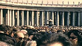 San Pietro crowd of believers in Rome. Vatican City, Rome, Italy - Circa 1970: crowd of believers in Saint Peter square of Rome, during the public speaking of stock video