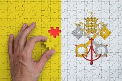 Vatican City State flag is depicted on a puzzle, which the man`s hand completes to fold.  vector illustration