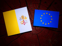 Vatican flag with EU flag on a tree stump isolated. Vatican flag with EU flag on a tree stump Royalty Free Stock Photo