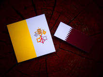 Vatican flag with Qatari flag on a tree stump isolated. Vatican flag with Qatari flag on a tree stump Royalty Free Stock Images