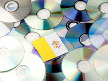 Vatican flag on top of CD and DVD pile isolated on white. Vatican flag on top of CD and DVD pile isolated Royalty Free Stock Photos