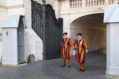 Vatican guards. VATICAN CITY, VATICAN - MAY 11: Famous Swiss Guard surveil basilica entrance on May 11, 2010 in Vatican. The Papal Guard with 110 men is the royalty free stock photo