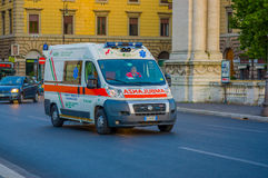 VATICAN, ITALY - JUNE 13, 2015: Ambulance van going fast on Rome streets, behind cars waitting.  Stock Image