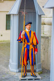 VATICAN, ITALY - JUNE 13, 2015: Swiss guard outside of Basilica at Vatican. Colorful and striped uniform considered one Stock Image