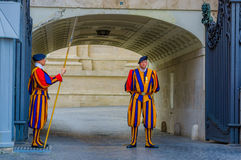 VATICAN, ITALY - JUNE 13, 2015: Swiss guard outside of Saint Peter Basilica at Vatican. Striped uniform considered one Royalty Free Stock Photos