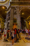 VATICAN, ITALY - JUNE 13, 2015: Tourists looking and taking photos inside Saint Peter Basilica at Vaticano, behind papal Stock Photography