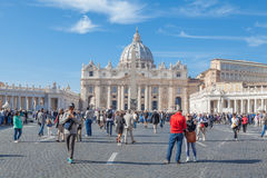 Vatican. Italy - November 7, 2015: The Papal Basilica of St. Peter against blue sky and its square with tourists Royalty Free Stock Image
