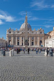 Vatican. Italy - November 7, 2015: The Papal Basilica of St. Peter against blue sky and its square with tourists Royalty Free Stock Photography