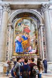 Paintings and mosaics in the Saint Peter basilica in Vatican. VATICAN - MARCH 13, 2016: Tourists admiring paintings made with tessera mosaic tile cubes in the royalty free stock images