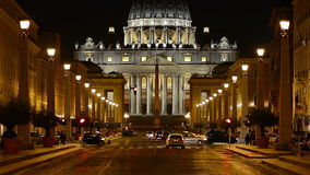 The Vatican at night. Night view of the Papal Basilica of Saint Peter in the Vatican (Basilica Papale di San Pietro in Vaticano). Vehicles passing across Via stock footage