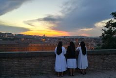 Vatican Nuns at Sunset. This pictures shows 3 nuns contemplating the Vatican on the background with a yellow light coming from behind the dome. One of the nun is stock photography