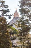 The dome of the Papal Basilica of St. Peter in the Vatican or simply St. Peter`s Basilica through the backyard garden trees. Vatican, Rome, Italy - November 16 stock photo
