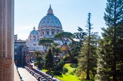 The dome of the Papal Basilica of St. Peter in the Vatican or simply St. Peter`s Basilica from backyard garden full of trees and. Vatican, Rome, Italy - November stock images