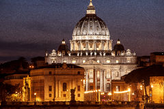 Vatican St. Peter at night. Vatican seen from bridge in Rome at night. Gold and blue colors in the sky and water. St. Peter seen in white Stock Photo