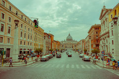 VATICANEN ITALIEN - JUNI 13, 2015: Den stora gatan med shoppar på sidorna, på den slutSt Peter basilikan i en molnig dag Arkivfoto