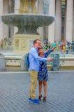 VATICANEN ITALIEN - JUNI 13, 2015: Oidentifierade par som tar selfiefoto i mitt av gatan, bak ett trevligt Royaltyfria Bilder