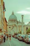 VATICANEN ITALIEN - JUNI 13, 2015: St Peter kupol på slutet av gatan på Rome, molnig dag med långa raden av bilar Arkivfoto