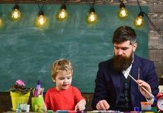 Vatikünstler, der seinem Sohn beibringt, wie man malt Blondes Kind, das lernt zu zeichnen Lizenzfreie Stockbilder