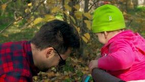 Vatispiele mit seiner kleinen Tochter, die in einem Spaziergänger sitzt stock video