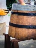 Vatrestauratie, een mens die een oud wijnvat schilderen Half vat voor installaties stock foto