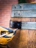 Vatrestauratie, een mens die een oud wijnvat schilderen Half vat voor installaties stock afbeeldingen