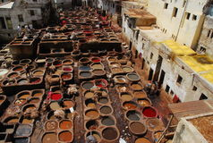 Vats in Fez, morocco. Workers tanning and dyeing in red hides in the vats of Fez tanneries, Morocco stock photography