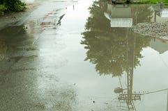 Vatten ackumulerar i pölen på asfaltvägen i hålet efter hällregn royaltyfri foto