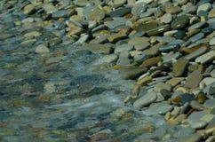 Vatten ackumulerar på den pebbly kusten Stranden av kiselstenar bac Royaltyfria Bilder