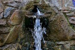 Vatten för att dricka flöden från gamla stenar tätt upp royaltyfri bild