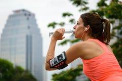 Vatten för den kvinnliga löparen för kondition vilar driking på genomkörare fotografering för bildbyråer