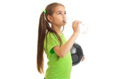 Vatten för drinkar för liten flickafotbollspelare från en flaska Royaltyfri Fotografi