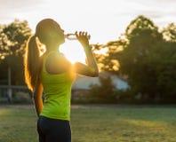 Vatten för löparekvinnadrink i stadion som utomhus övar wearable teknologi för konditionbogserare Royaltyfri Fotografi