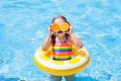 vatten för simning för barnpölsport äta ungeorangen arkivbilder