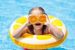 vatten för simning för barnpölsport äta ungeorangen Arkivbild