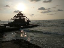 Vatten för solnedgångstrandhav med unfinish byggnad Fotografering för Bildbyråer