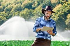 Vatten för sprinkleranläggning för hatt för teknologi för koloni för dator för minnestavla för kontroll för arbetare för sol för  arkivbild