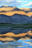 vatten för bergreflexionssolnedgång Arkivfoton