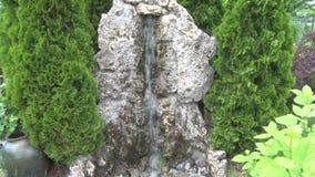 Vatten faller på en dekorativ sten i borggården arkivfilmer