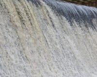 Vatten flödar över en malafördämning Royaltyfria Foton