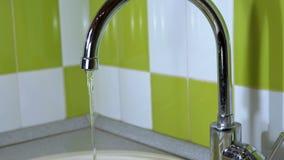 Vatten flödar från ett klapp in i en vask stock video