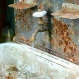 Vatten flödar från ett retro rörmokeriklapp in i en gammal vask Tappning arkivfoton